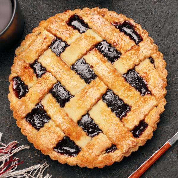 Une tarte aux mûres déposée sur une table avec une fourchette, un couteau et deux tasses de café.