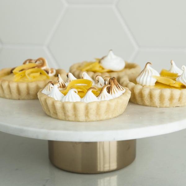 Des tartelettes citron-ananas meringuées servies sur un piédestal à gâteau.