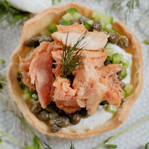 Une tartelette au saumon fumé garnie d'aneth, et entourée d'herbes fraîches et de quenelles de labneh.