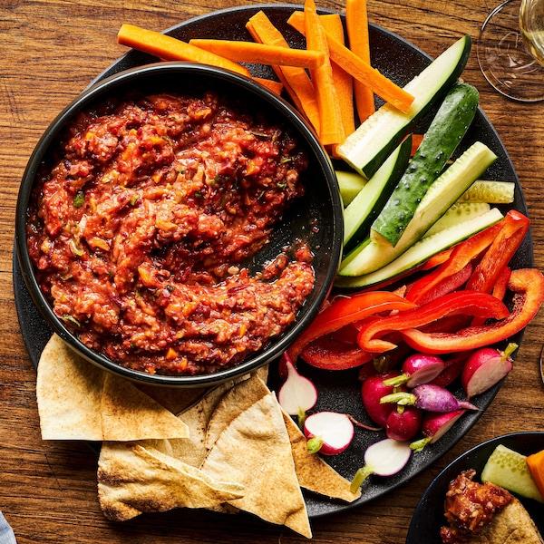 Tartinade de haricots rouges aux tomates rôties dans un bol avec des crudités dans une assiette.