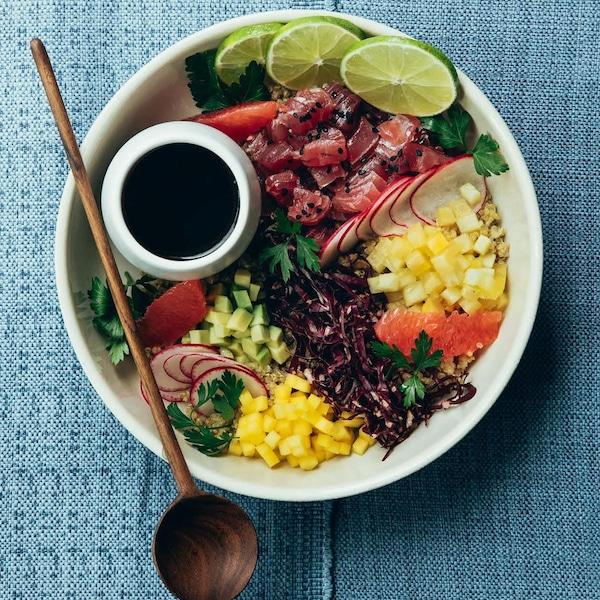 Un poké de thon et quinoa au jus d'agrumes garni de légumes colorés.
