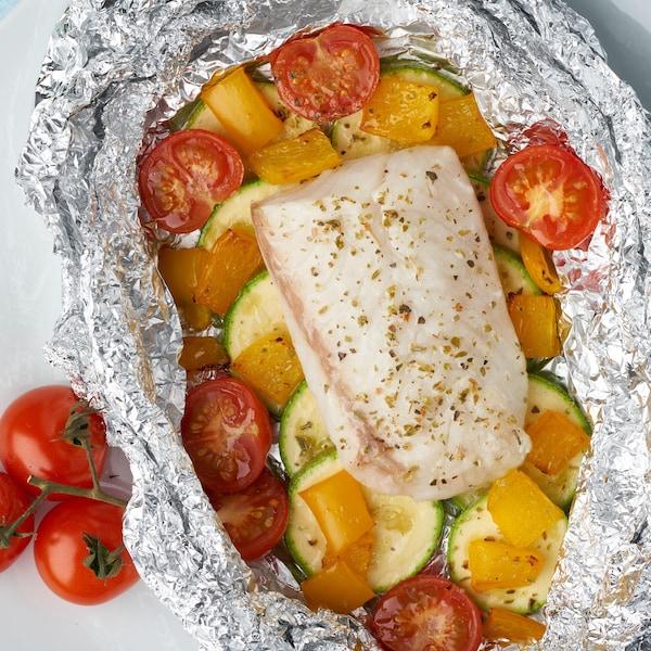 Un morceau de tilapia sur un lit de courgettes et de tomates.