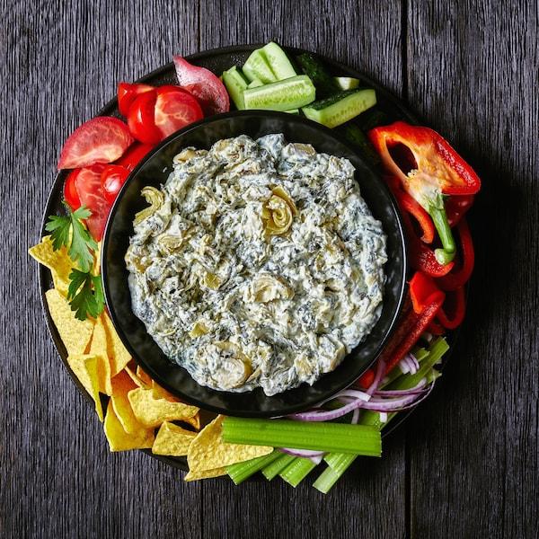 Un bol rempli de trempette aux épinards entouré de plusieurs légumes et croustilles.