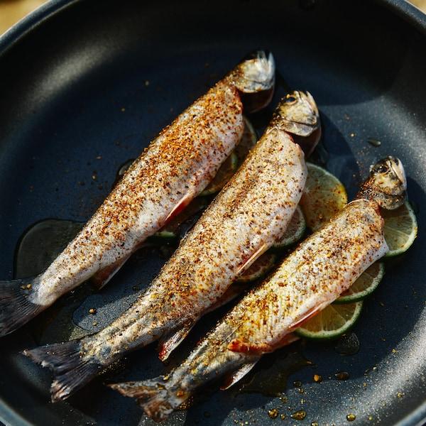 Dans une poêle, est déposé trois petites truites assaisonnées d'épices cajun et de morceaux de lime.