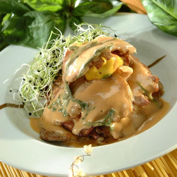 Une assiette avec une escalope de veau napée de crème de basilic.