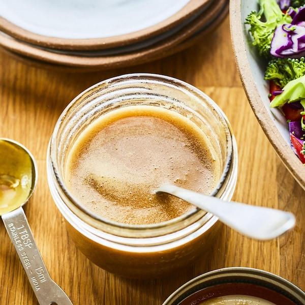 Pot de vinaigrette posé sur une table en bois à côté d'un grand saladier.