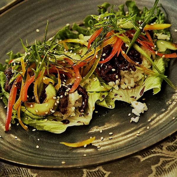 Plusieurs légumes et du bison sur des feuilles de salade.