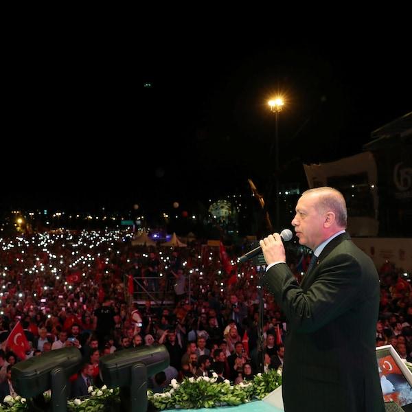 Un homme s'exprimant dans un micro devant une foule brandissant des drapeaux turcs