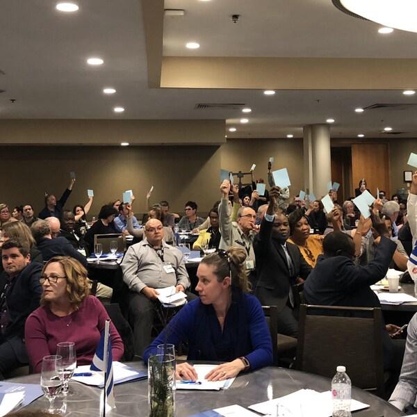 Des gens dans une salle, certains levant un papier pour voter.