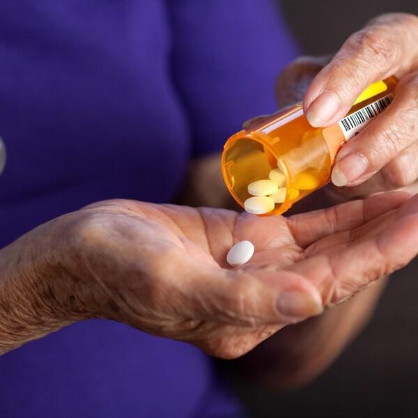 Une dame prend une pilule.