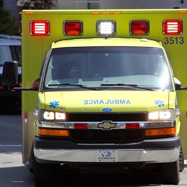Une ambulance vue de face, dans les rues en été.