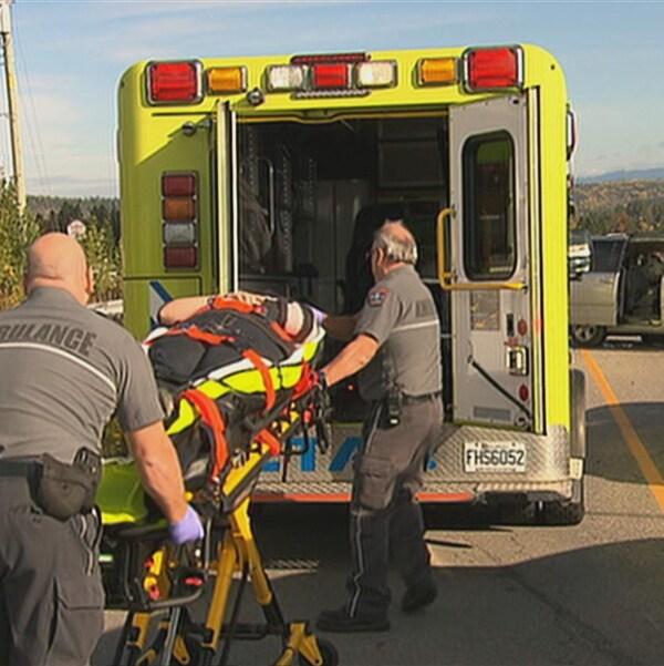 Deux paramédics transportent une civière dans l'ambulance.
