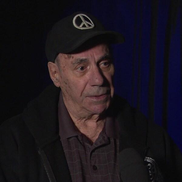 Un homme âgé et portant une casquette parle en entrevue.