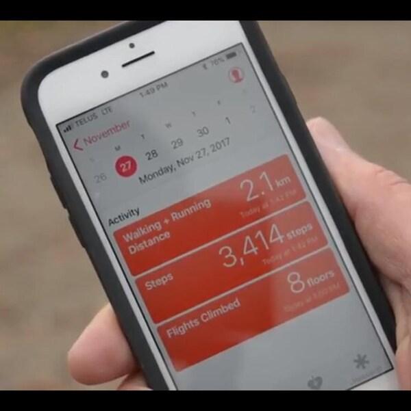 Un téléphone cellulaire de type iPhone affichant un calendrier et une liste d'activités physiques accomplies.