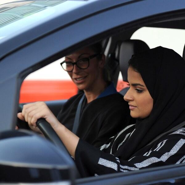 Une femme portant un voile noir est au volant d'une voiture accompagnée d'une autre femme portant des lunettes.