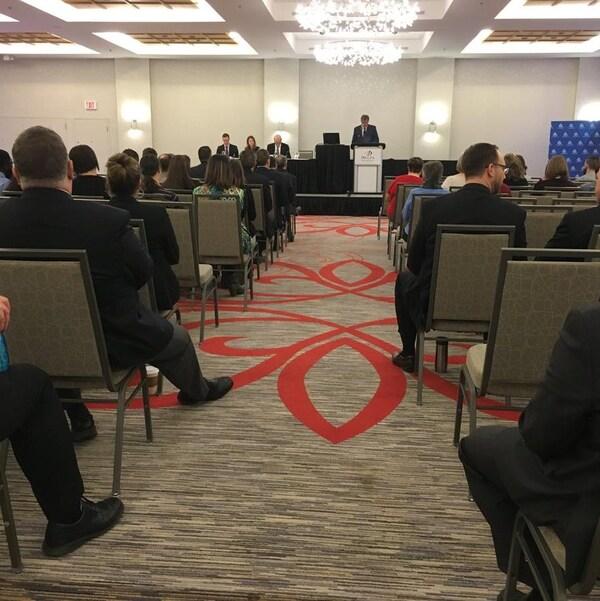 Des gens d'affaires dans une salle de conférence écoutent la présentation des résultats financiers.