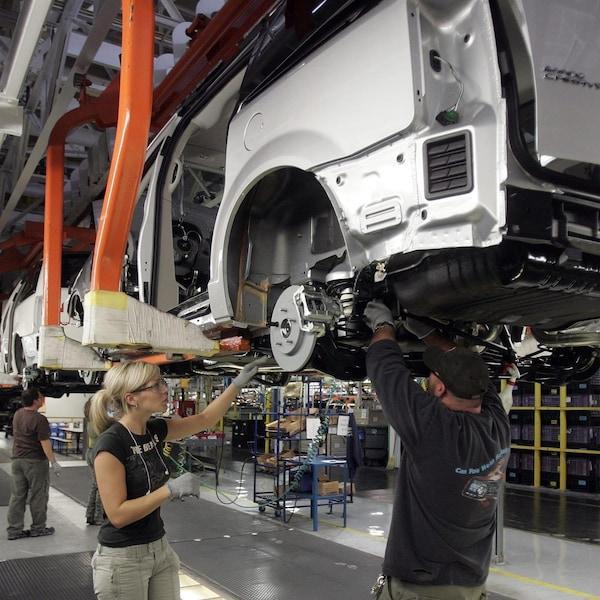 Un homme et une femme travaillent dans une usine d'assemblage du groupe Fiat Chrysler Automobiles à Windsor, en Ontario.