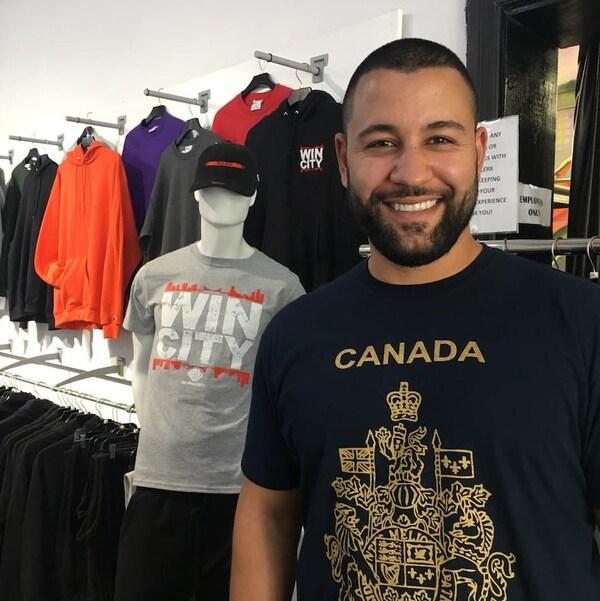 Portrait d'un homme souriant. Il est debout dans un magasn de vêtements. Des t-shirt et chandails sont suspendus au mur et sur des portants