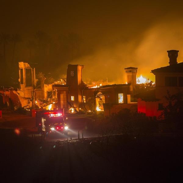En pleine nuit, un feu de forêt brûle une maison devant laquelle se trouve un camion de pompiers.