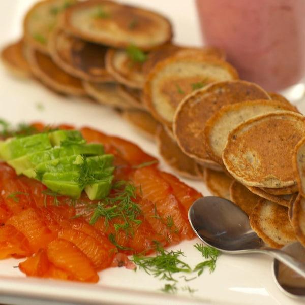 Des blinis et des tranches de saumon gravlax sur une grande assiette.