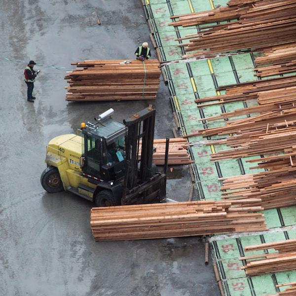 Les piles de bois scié sont assemblées à l'aide d'un gerbeur.