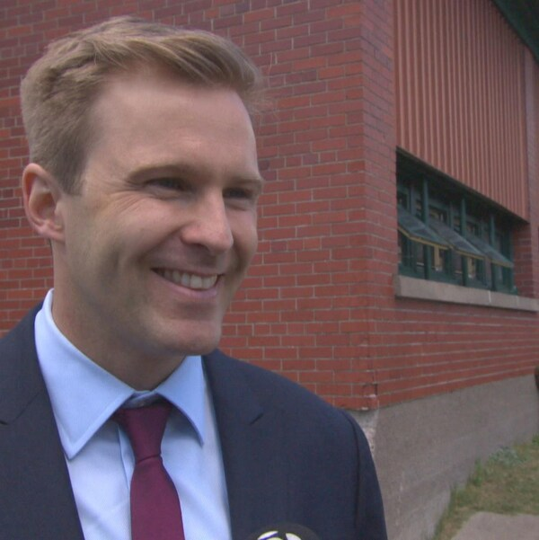 Le politicien en entrevue, à l'extérieur. Il est souriant.