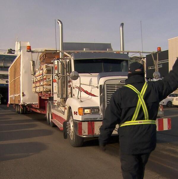 Des employés de la Société des traversiers du Québec aident les camionneurs à reculer dans le F-A Gauthier.