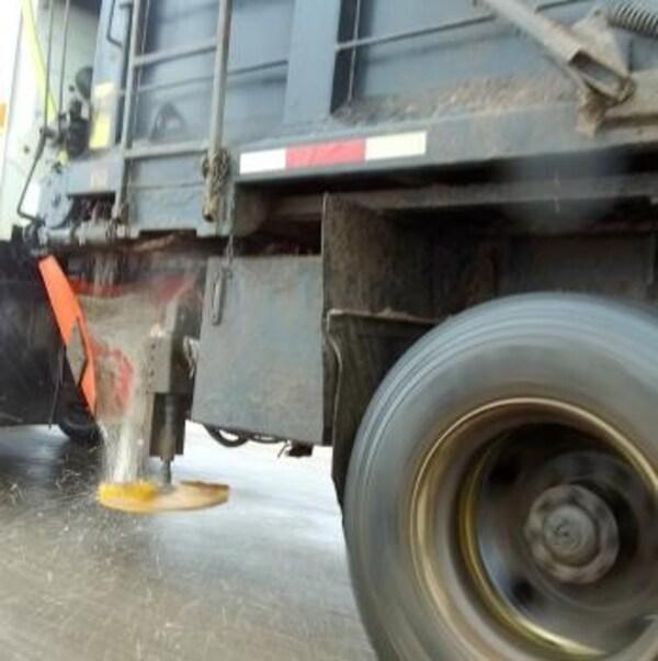 Un camion répand du sel sur une route.