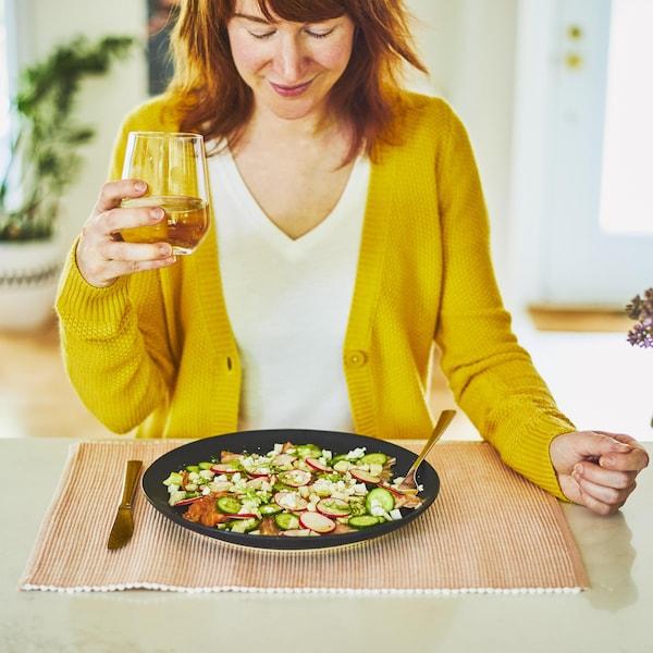 Une femme est attablée devant une assiette de carpaccio dans sa demeure.