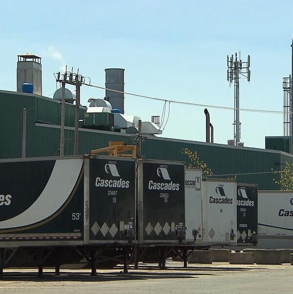 Des remorques pour des camions de livraison de la compagnie Cascades devant une usine.