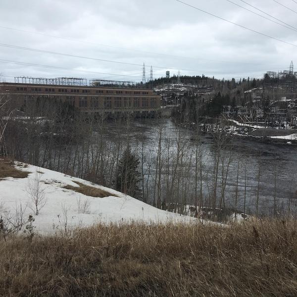 Une centrale hydroélectricité en brique. Il y a un plan d'eau entourant d'arbres et de neige.