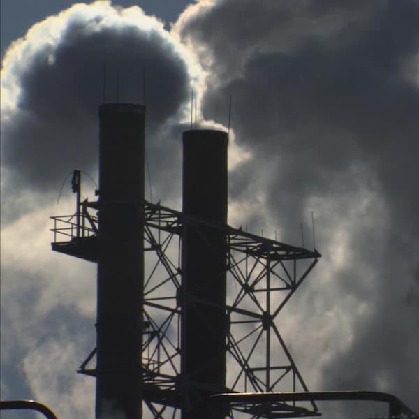 Des cheminées rejettent une épaisse fumée blanche.