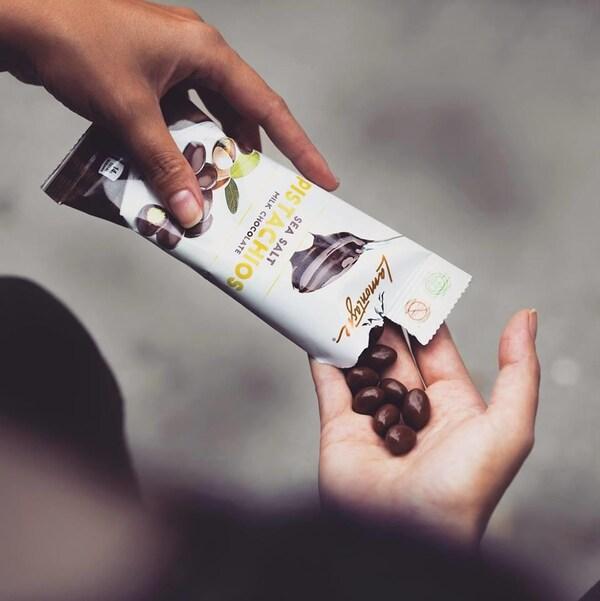 L'un des produits de Chocolat Lamontagne, des pistaches au chocolat et sel de mer. On voit ici quelqu'un se servir dans un paquet déjà ouvert.