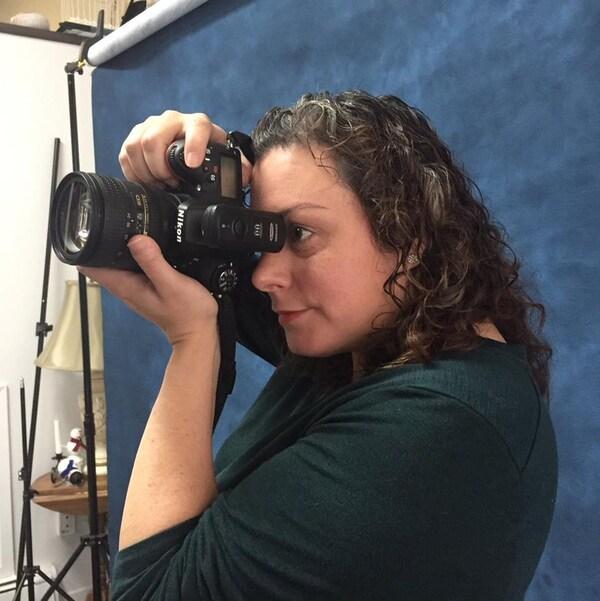 Chrissie Green pointe sa caméra vers un sujet à photographier.