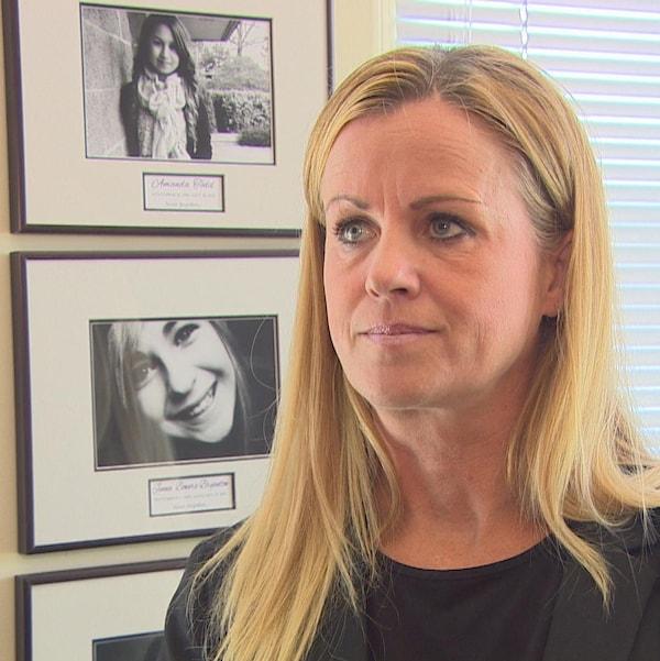 Une femme portant un veston noir devant des cadres où sont exposées des photos en noir et blanc.