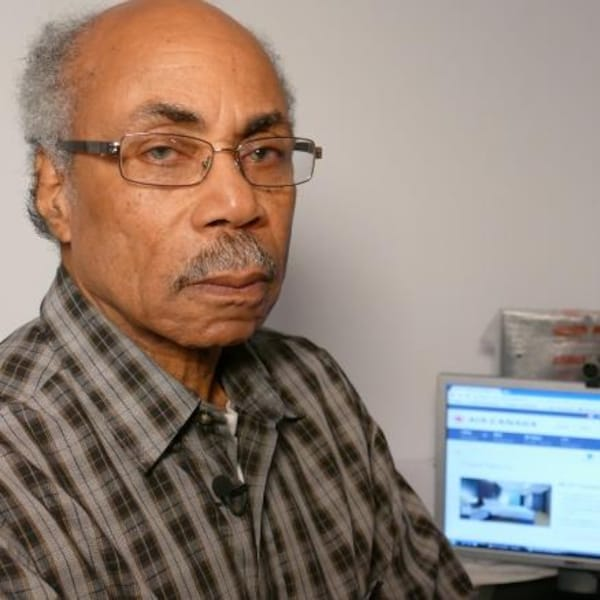 Claude Neblett, stoïque, devant un écran d'ordinateur.