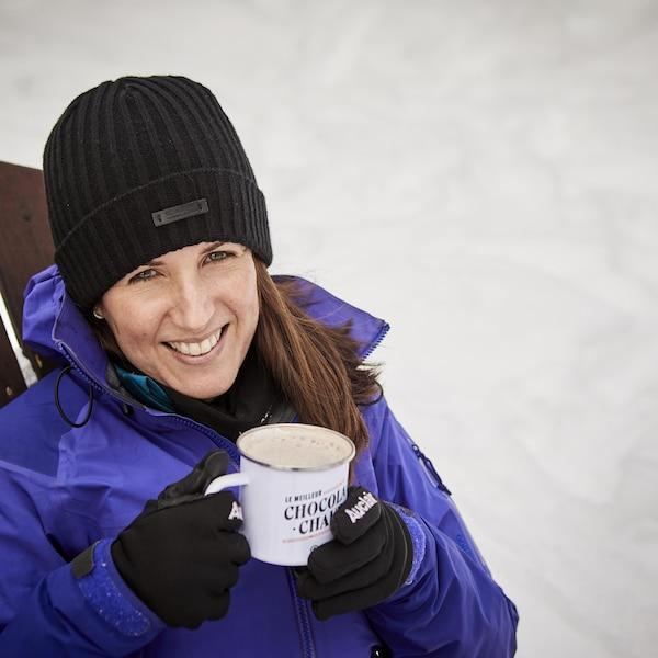Geneviève O'Gleman boit un chocolat chaud assise sur une chaise à l'extérieur, en hiver.