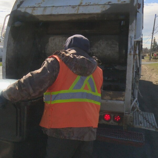 Un homme s'apprête à vider un bac d'ordures dans le camion.