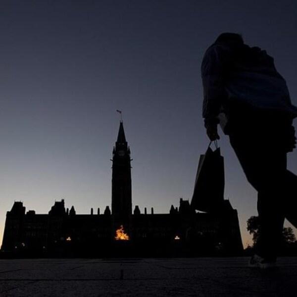 Des personnes devant la colline du Parlement de nuit.