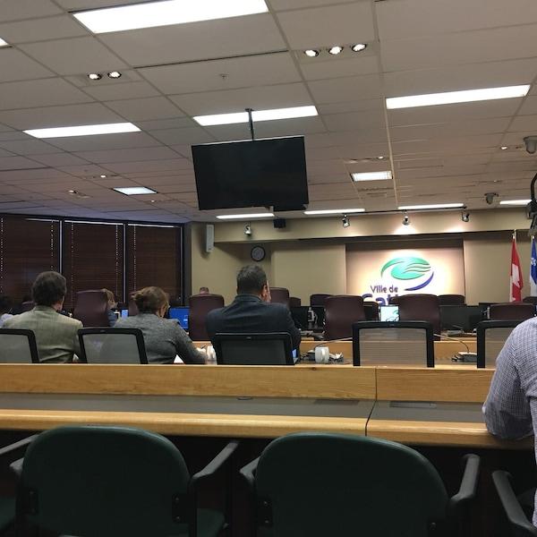 La photo montre la salle du conseil municipal où se tient la réunion du comité exécutif qui accorde à son service juridique le mandat de poursuivre la firme de génie-conseil.