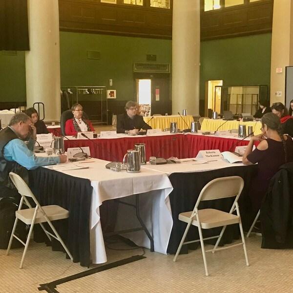 Une salle au  milieu de laquelle il y a une table carrée avec des gens assis autour.