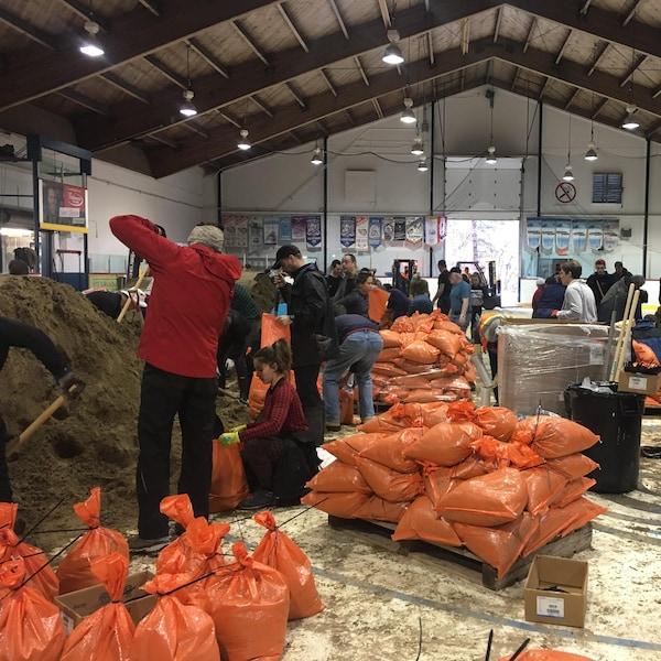 Des sacs oranges remplis de sable avec des bénévoles qui les remplissent