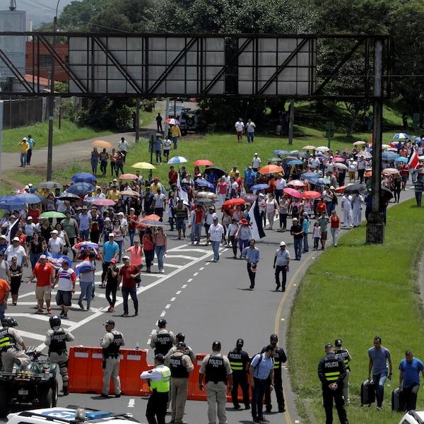 Une longue file de gens, presque tous portant des parapluies pour se protéger du soleil, bloquent la route, devant un petit barrage de police.
