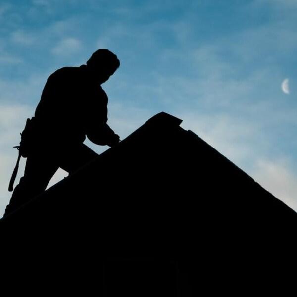 Un couvreur à contre-jour au sommet d'un toit