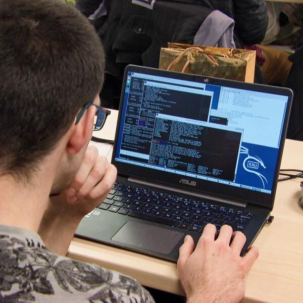 Un étudiant de dos travaille à un ordinateur portable.