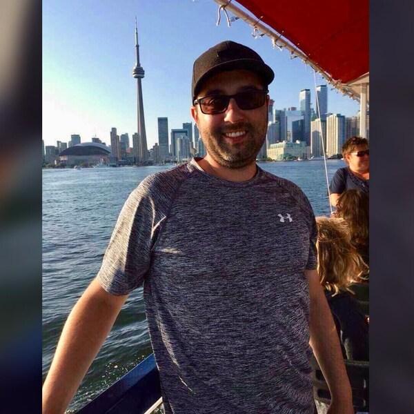 Un homme de 30 ans sur un bateau devant des immeubles à Toronto.