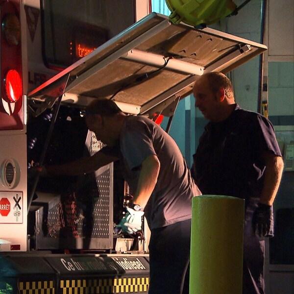 Deux hommes inspectent un moteur d'autobus de la STM.