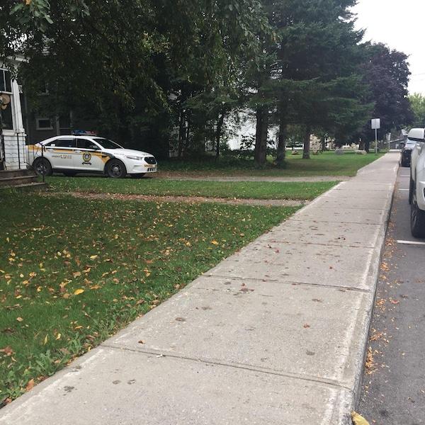 Une rue de Lac-Brome avec une voiture de police de la SQ.