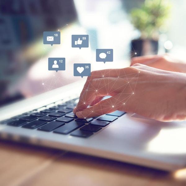 Une personne tape sur le clavier d'un ordinateur et des émoticônes apparaissent sur la photo.