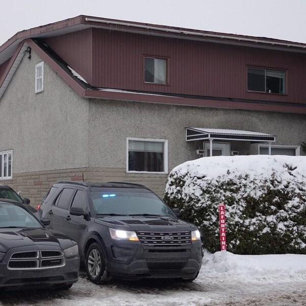 Deux voitures du FBI dans l'entrée d'une maison.